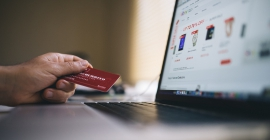 person using laptop and holding a credit card