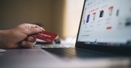 hand holding credit card while online shopping